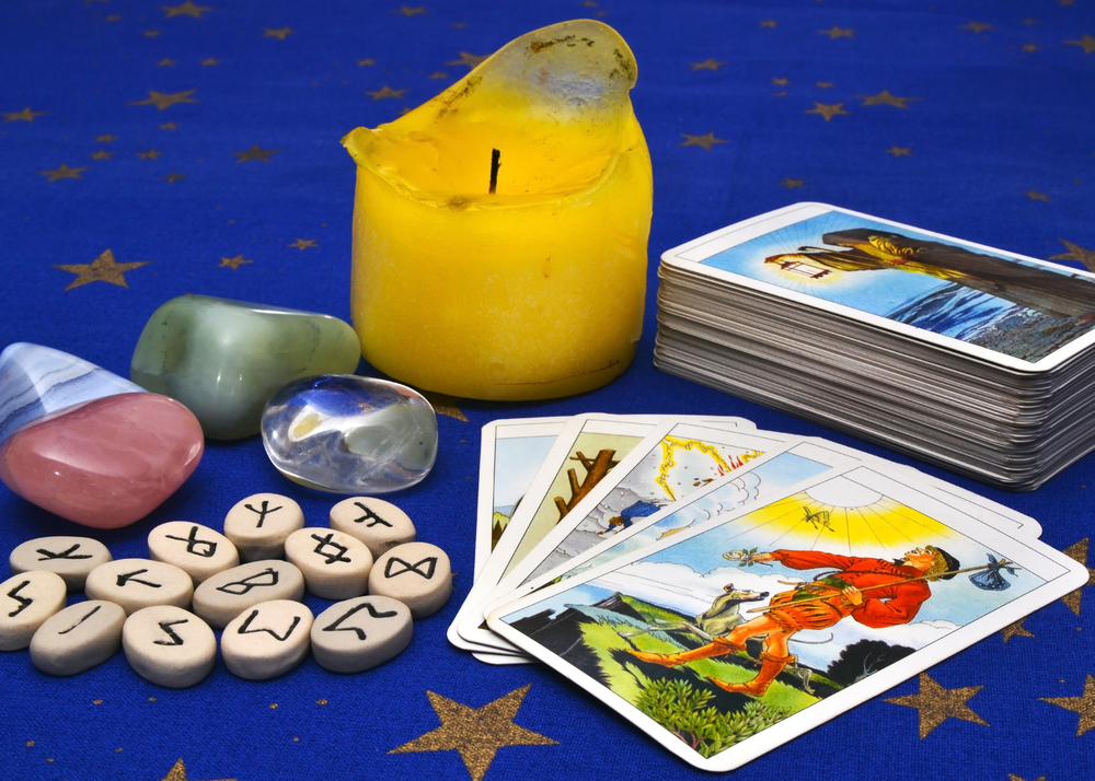 Items for divination - tarot cards, rune stones, healing crystals and candle